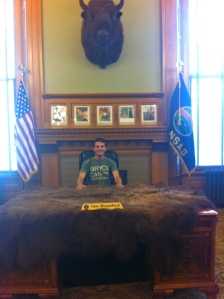 At Governor Sam Brownback's desk in Topeka, Kansas. The buffalo hide is real and was given to the governor by a local Indian chief.