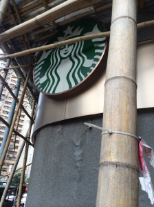 This pictures sums up Hong Kong: Starbucks and bamboo scaffolding